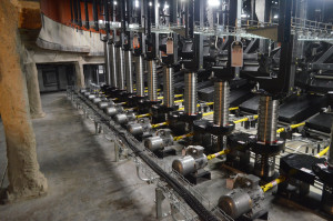 View of the machinery room under seating at H-E-B Performance Hall at Tobin Center in San Antonio. The motor at the end of each platform can be seen with a (yellow) shaft connecting each lift mechanism.  Photo by Paul Sanow ASTC